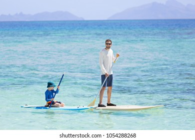 family of two, little boy and young father, enjoying stand up paddleboarding together, active family vacation concept
