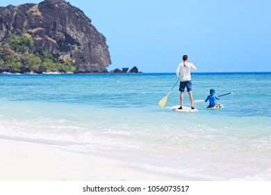 family of two, little boy and young father, enjoying stand up paddleboarding together at fiji, active family vacation concept