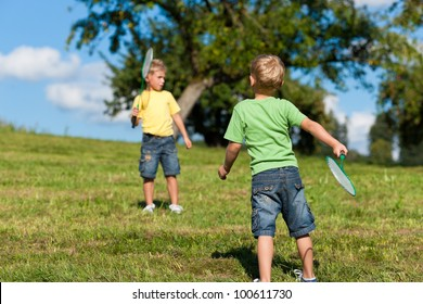 Family - two little boys playing badminton outdoors