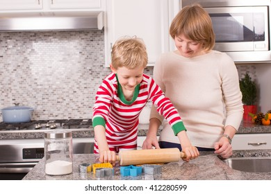 family of two, mother and son, being cozy at home at christmas time and making gingerbread cookies together