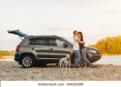 Family of two person and dog embrace near car on sunset river