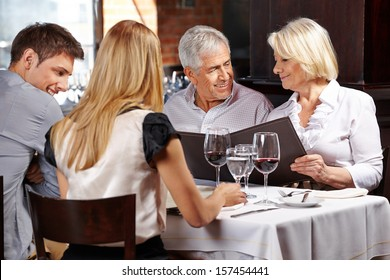 Family with two senior people in restaurant holding the menu