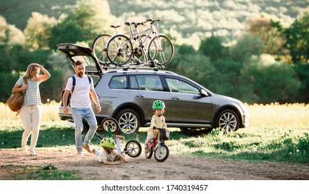 Family with two small children going on cycling trip in countryside.