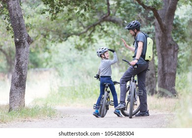 family of two, young father and cheerful son, enjoying bike riding, kid giving high five to his dad, active family concept