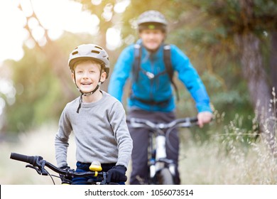 family of two, young father and cheerful son, enjoying bike riding, active family concept