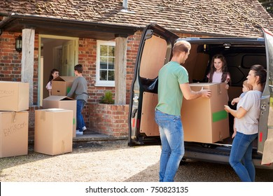 Family Unloading Boxes From Removal Truck On Moving Day
