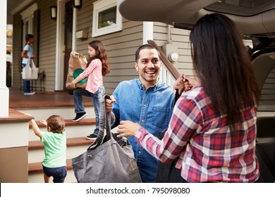 Family Unloading Shopping Bags From Car