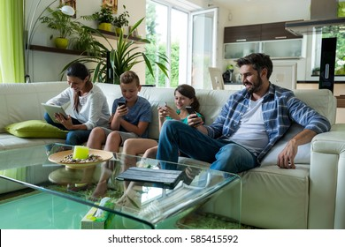 Family using laptop and mobile phone in living room at home