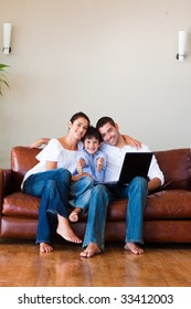 Family using a laptop with thumbs up on a couch with copy-space