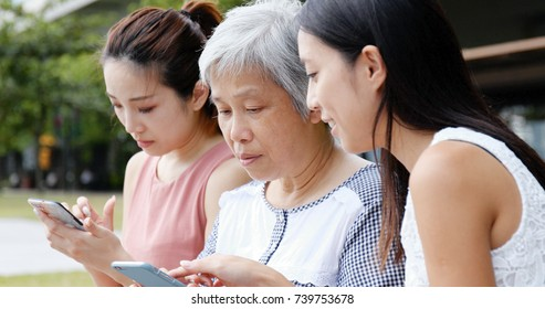 Family using mobile phone together at outdoor park