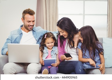 Family using modern technologies while sitting on sofa at home