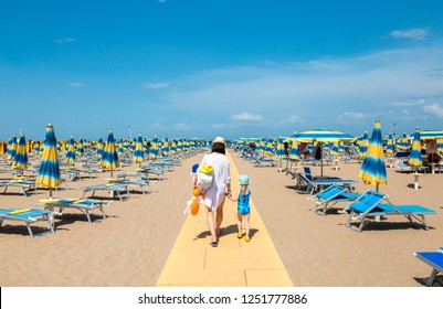Family vacation background. Mother with kid going on beach to the sea. Rimini, Italy.
