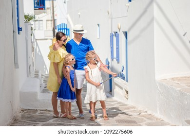 Family vacation in Europe. Parents and kids taking selfie photo in old street on Mykonos town in Greece