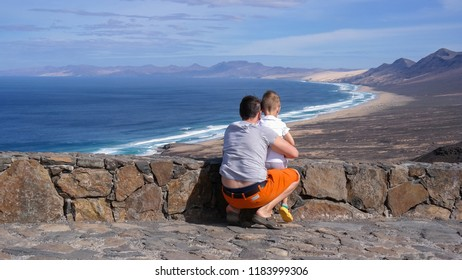 Family Vacation in Fuerteventura. Father and son look at the beautiful landscape. Happy together.