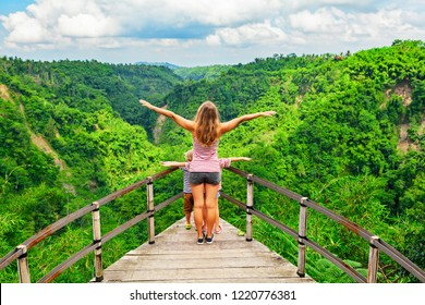 Family vacation lifestyle. Happy woman with kids stand on edge of overhanging bridge on high cliff above. People looking at stunning jungle view. Tukad Melangit is popular travel destination in Bali.