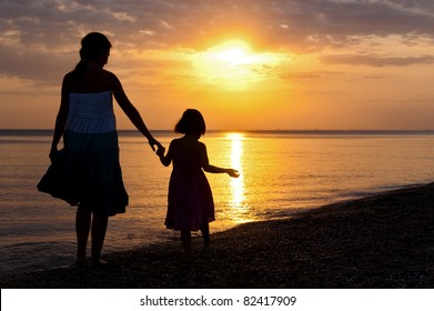 Family vacation. Mother and kid on sunset beach