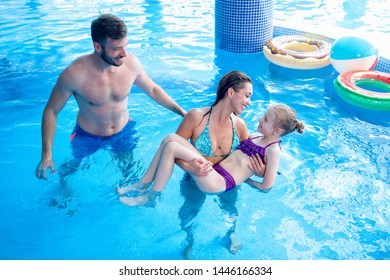 Family vacation and play time in the swimming pool, happy family playing together