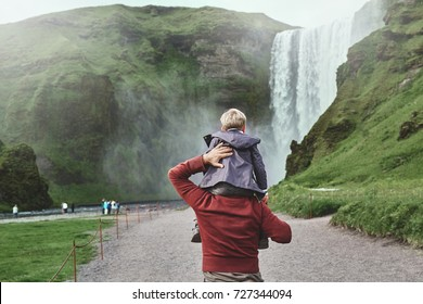 family in vacation traveling in Iceland. father carries a small son on his shoulders to the famous waterfalls of Skogafoss