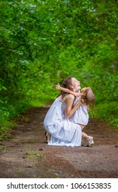 Family Values Concepts. Happy Caucasian Woman with Her Little Child Pembracing in Green Forest. Posing in White Dresses.Vertical Shot