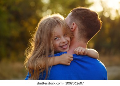 Family values. The daughter hugs her father and shows her tongue.