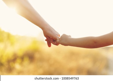 Family values. The father holds his daughter's hand. Hand in hand. Child support. Walk at sunset.