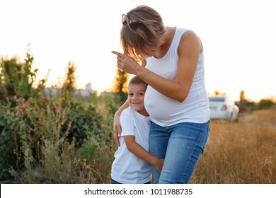 Family values. Pregnant mother and son are walking in the field at sunset. She shows the boy somewhere, and the son hugs her leg.