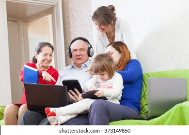 family of with various portable computers on sofa at home