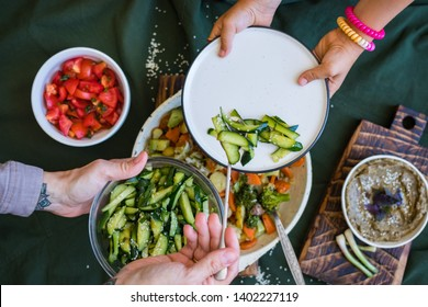 Family vegan lunch or vegetarian dinner. Mother hands put vegetables on dish, gives salad to child, kid. Healthy food. Top above view on table.