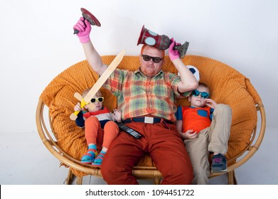 Family viewing of football match on TV. Elderly father with football cup in his hands and children with football and wooden sword in his hands. Sunglasses and TV remote. Bright emotions of fan.