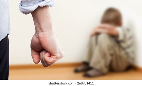 Family violence and aggression concept - furious angry man raised punishment fist over scared or terrified child boy sitting at wall corner