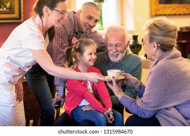 Family visit in a retirement home, nurse bringing tea
