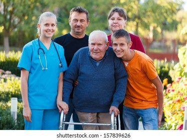 Family visiting grandfather at the nursing home, helping him with the walker.