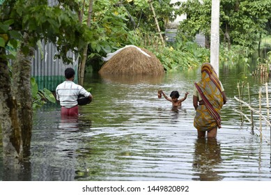A family  wade through a flooded road  to residence, at Kalgachia of Barpeta district of Assam, India on July 12, 2019.