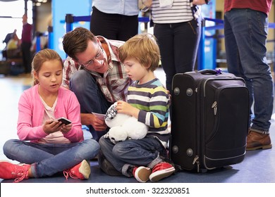 Family Wait In Queue At Airport Check In