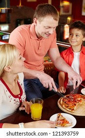 Family waiting for their father to cut an appetizing pizza in pieces