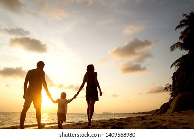 family walk along the beach at sunset with his son: back view silhouette