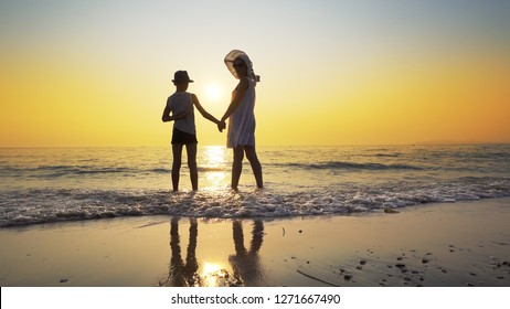 Family walk on beach to sea sunset and splash waves. Woman wear white dress and straw hat, boy has hat