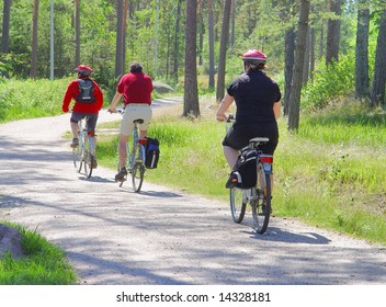 Family walk on bicycles on wood road
