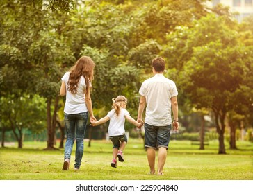 Family walk in the park, happy at sunset in Bangkok, Thailand.