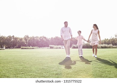 Family walk. Family of three walking on grassy field smiling che