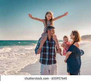 family walkig the beach with children in summer