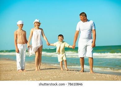 Family walking along the beach while on vacation