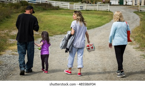 Family walking along gravel road after having picked apples at an apple farm