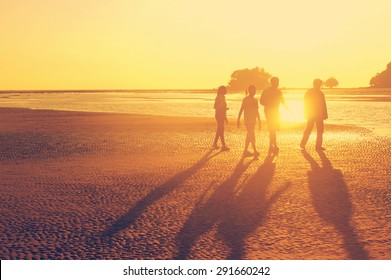 The family walking at the beach during sunset time, orange sun light, like instagram filter effect. Concept of happy family, Using the time with the one we love