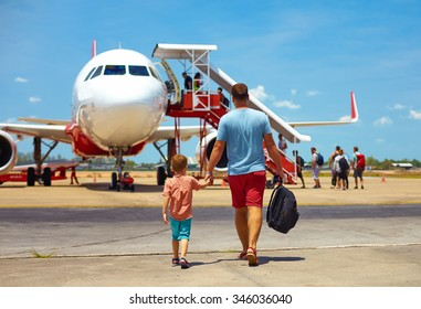 family walking for boarding on plane in airport, summer vacation