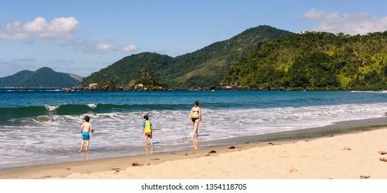Family walking by the beach in Ilhabela, Braz