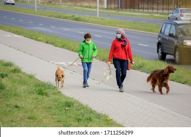 Family walking dog during virus outbreak. Mother and son in masks walking the dog outside the house during covid-19. Corona virus concept