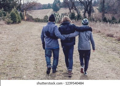 Family walking down a path while searching for a Christmas tree
