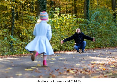 Family walking in the forest on a sunny autumn day. Father and daughter enjoying time together at fall. Beautiful little girl in blue coat playing in the park.