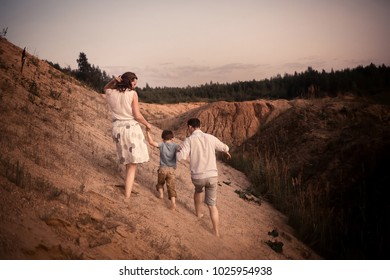 Family is walking and having fun together on the sand opencast during sunset. Image with selective focus, noise effect and toning.
